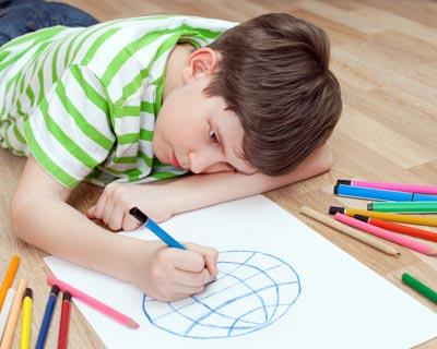 عکس یک پسربچه روی زمین که یک عکس را ترسیم می کند