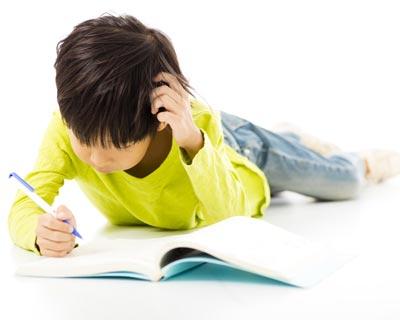 عکس پسری روی زمین که کتاب می خواند
